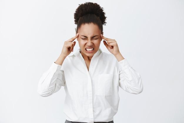 すべての脳力で考える。集中して計画を立てようとしているときに、ホワイトカラーシャツに黒い肌をした、歯を食いしばり、緊張を高めた、集中力のある深刻な格好の女性の肖像画
