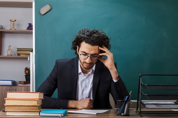 Thinking with lowered head male teacher wearing glasses sitting at table with school tools in classroom