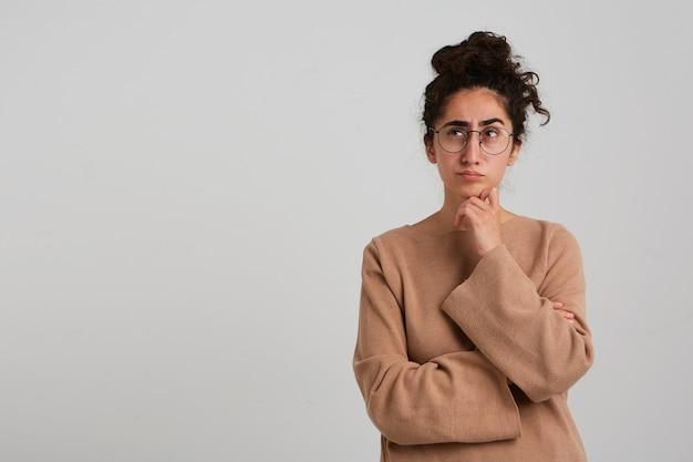 Думающая женщина, красивая девушка с темным пучком вьющихся волос, в бежевом джемпере и очках