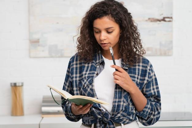 ノートとペンを保持している思考の女性