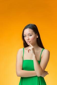 緑のドレスで考える女性