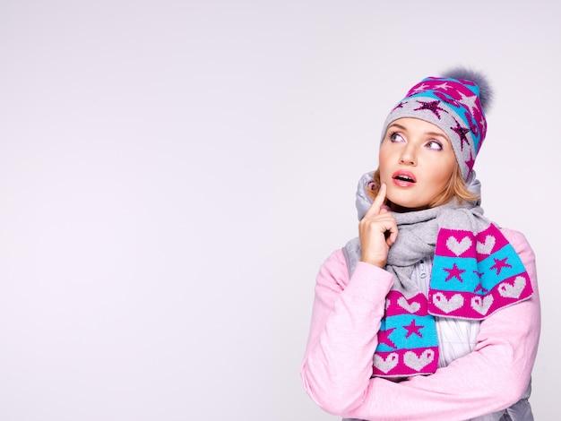 Думающая женщина в зимней одежде смотрит вверх