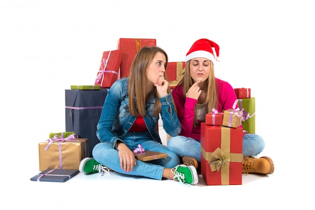 Thinking women with gifts over white background
