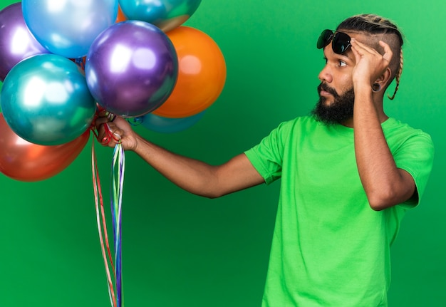 Thinking young afro-american guy wearing glasses holding and looking at balloons