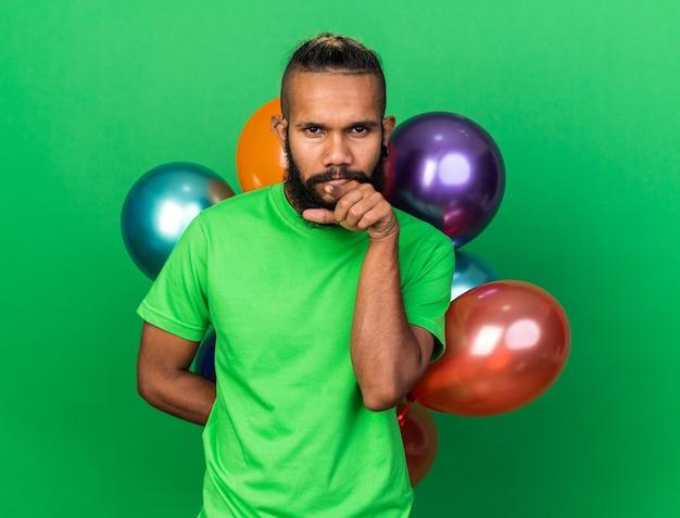 Pensare che un giovane afroamericano che indossa una maglietta verde in piedi davanti a palloncini punta alla telecamera