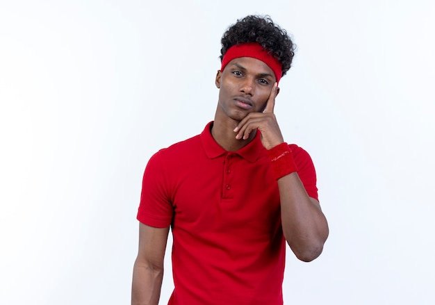 Thinking young afro-american sporty man wearing headband and wristband putting finger on face isolated on white