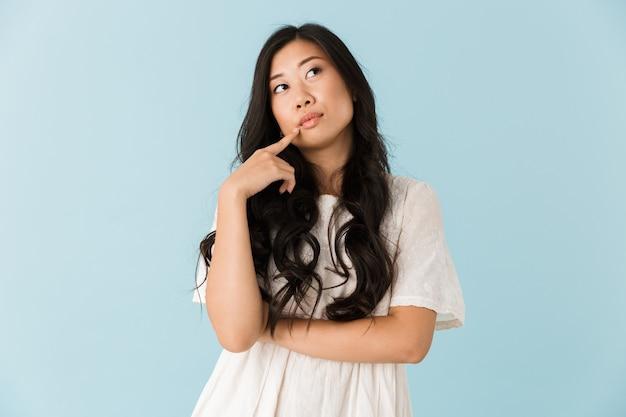 Думая молодая азиатская красивая женщина позирует изолированной над синей стеной