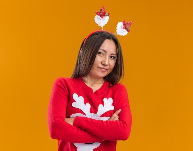 Думающая молодая азиатская девушка в рождественском обруче для волос со свитером, скрещивающим руки, изолирована на оранжевой стене