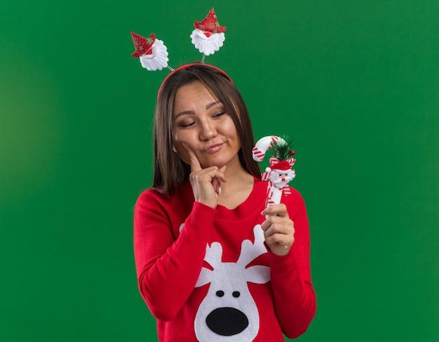 스웨터를 들고 녹색 배경에 고립 된 크리스마스 사탕을보고 크리스마스 머리 후프를 입고 생각 젊은 아시아 여자