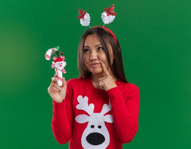 녹색 배경에 고립 뺨에 손가락을 넣어 크리스마스 사탕을 들고 스웨터와 크리스마스 머리 후프를 입고 생각 젊은 아시아 여자