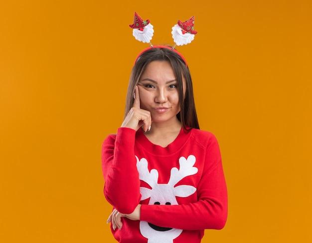 Giovane ragazza asiatica di pensiero che porta il cerchio dei capelli di natale con il maglione che mette il dito sulla guancia isolata sulla parete arancione