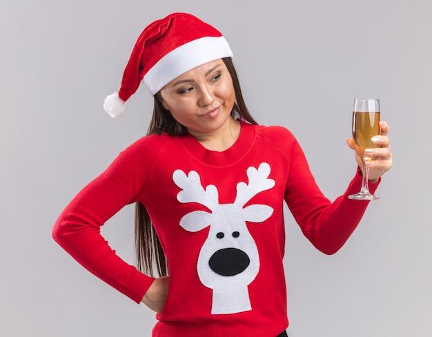 흰색 배경에 고립 된 손 o 엉덩이를 넣어 샴페인 잔을 들고 스웨터와 크리스마스 모자를 쓰고 생각 젊은 아시아 여자
