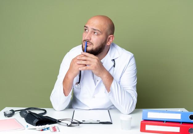 녹색 벽에 고립 된 입에 펜을 넣어 의료 도구와 책상 작업에 앉아 의료 가운과 청진기를 입고 생각 젊은 대머리 남성 의사