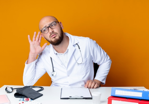 Thinking young bald male doctor wearing medical robe and stethoscope in glasses sitting