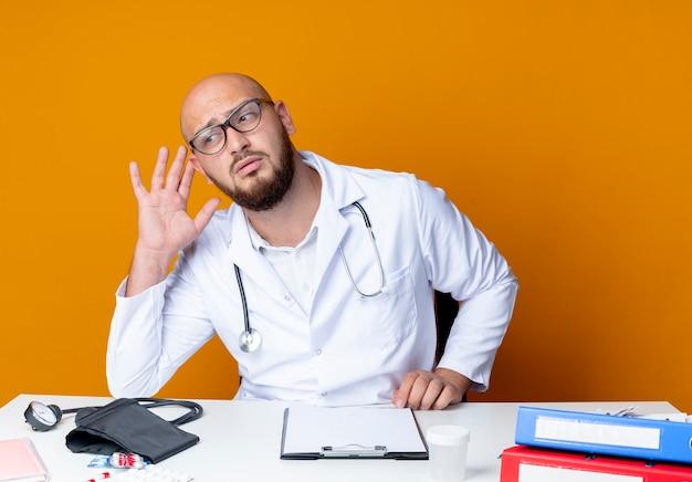 Giovane medico maschio calvo di pensiero che indossa veste medica e stetoscopio in vetri che si siedono