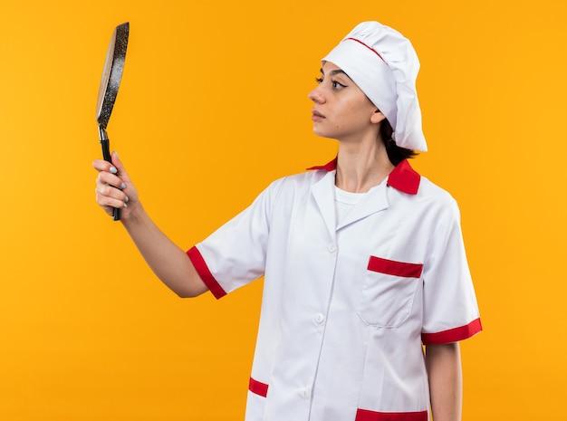 Думая молодая красивая девушка в униформе шеф-повара, держащая и смотрящую на сковороду, изолированную на оранжевой стене