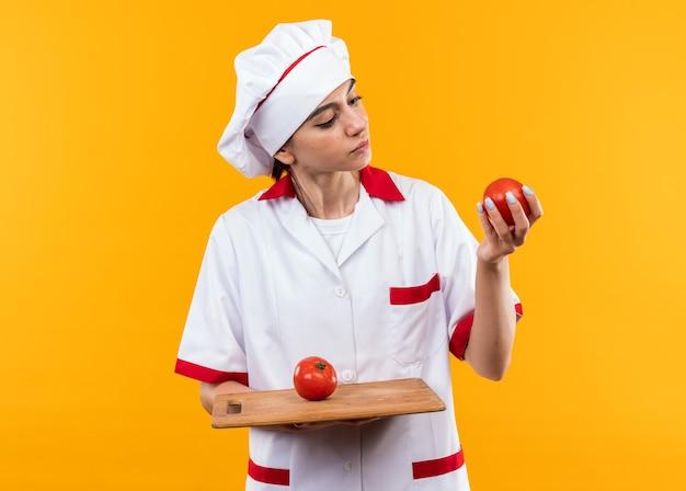 Думая молодая красивая девушка в униформе шеф-повара, держащая и смотрящую на помидоры на разделочной доске