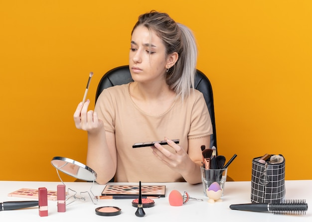 考える若い美しい少女は、オレンジ色の背景に分離された化粧ブラシでアイシャドウパレットを保持し、見ている化粧ツールでテーブルに座っています