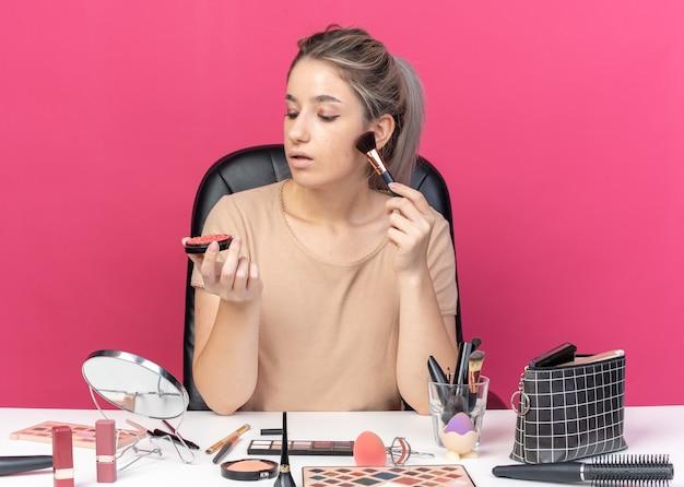 La giovane e bella ragazza pensante si siede al tavolo con gli strumenti per il trucco applicando il fard in polvere isolato su sfondo rosa
