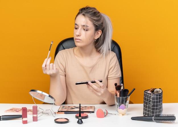 La giovane e bella ragazza pensante si siede al tavolo con gli strumenti per il trucco che tengono e guarda la tavolozza dell'ombretto con il pennello per il trucco isolato su sfondo arancione