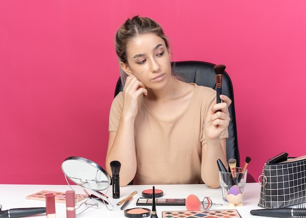 Thinking young beautiful girl sits at table with makeup tools holding and looking at powder brush isolated on pink background