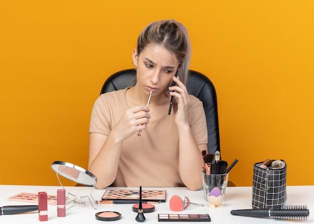 Pensare che la giovane bella ragazza si siede al tavolo con gli strumenti per il trucco che tengono il pennello per il trucco parla al telefono isolato su sfondo arancione