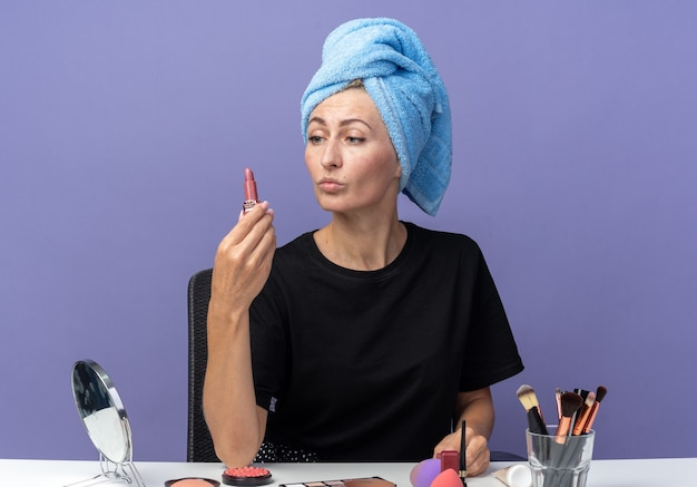 Thinking young beautiful girl sits at table with makeup tools wiping hair in towel holding and looking at lipstick isolated on blue background