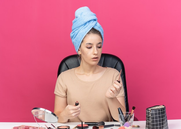 Thinking young beautiful girl sits at table with makeup tools wrapped hair in towel holding and looking at lipgloss isolated on pink background