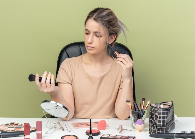 Pensando giovane bella ragazza seduta alla scrivania con strumenti per il trucco tenendo e guardando il pennello per il trucco isolato su sfondo verde oliva