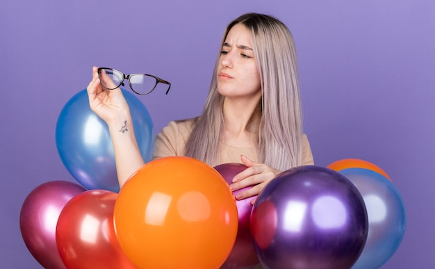 Thinking young beautiful girl standing behind balloons holding and looking at glasses