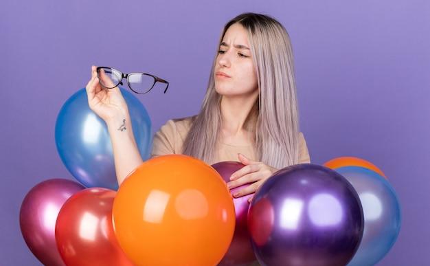 眼鏡を持って見て風船の後ろに立っている若い美しい少女を考える