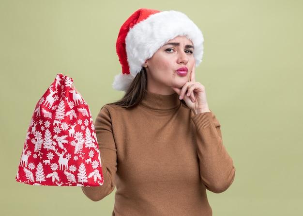 Giovane bella ragazza di pensiero che porta il cappello di natale che tiene la borsa di natale che mette il dito sulla guancia isolata su fondo verde oliva