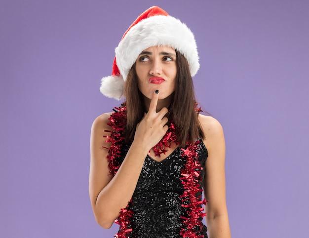 Pensando giovane bella ragazza che indossa il cappello di natale con la ghirlanda sul collo mettendo il dito sul mento isolato su sfondo viola