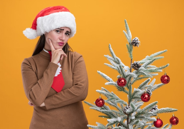 Pensando giovane bella ragazza che indossa il cappello di natale con cravatta in piedi vicino albero di natale mettendo il dito sulla guancia isolato su sfondo arancione