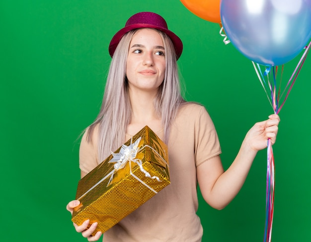 Thinking young beautiful girl wearing party hat and braces holding balloons holding gift box isolated on green wall