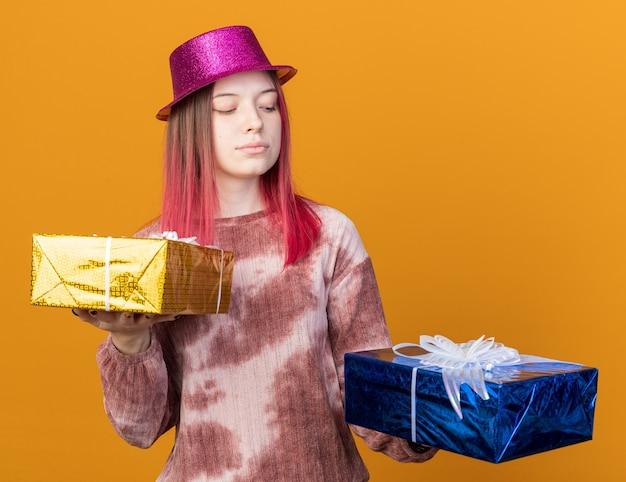 오렌지색 벽에 격리된 선물 상자를 들고 보고 있는 파티 모자를 쓰고 생각하는 젊은 아름다운 소녀
