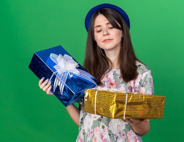 Думая молодая красивая девушка в партийной шляпе, держа и глядя на подарочные коробки