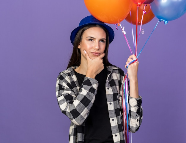 Thinking young beautiful girl wearing party hat holding balloons grabbed chin isolated on blue wall