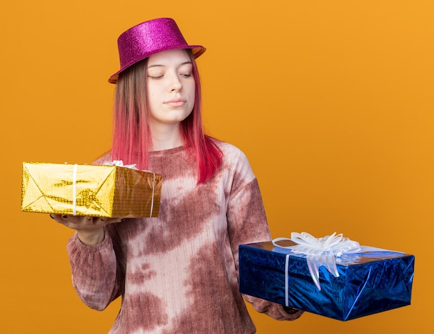 Thinking young beautiful girl wearing party hat holding and looking at gift boxes isolated on orange wall