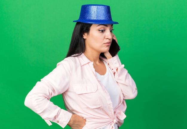 파티 모자를 쓴 아름다운 소녀가 녹색 벽에 격리된 엉덩이에 손을 대고 전화 통화를 하고 있다고 생각합니다.