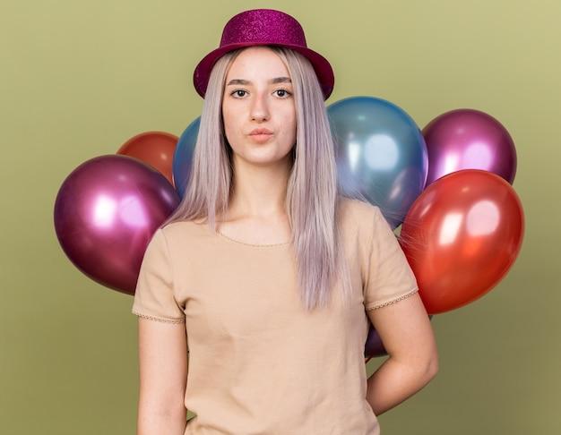 올리브 녹색 벽에 격리된 풍선 뒤에 서 있는 파티 모자를 쓰고 생각하는 젊은 아름다운 소녀