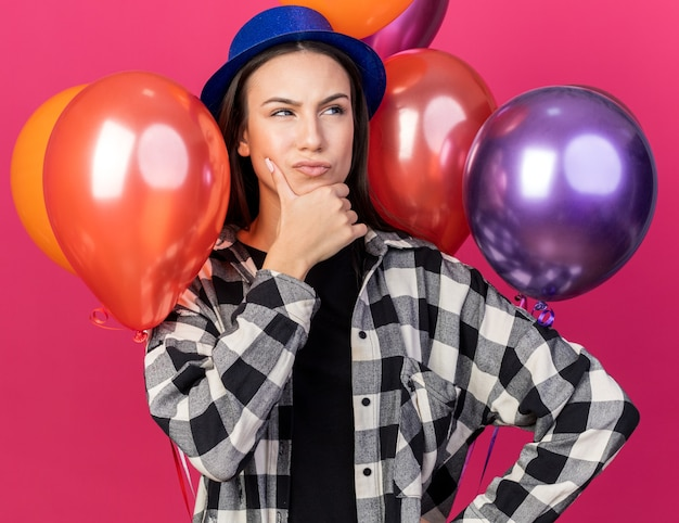 Thinking young beautiful girl wearing party hat standing in front balloons grabbed chin