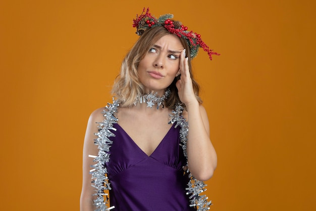 Thinking young beautiful girl wearing purple dress with wreath putting hand on temple isolated on brown background