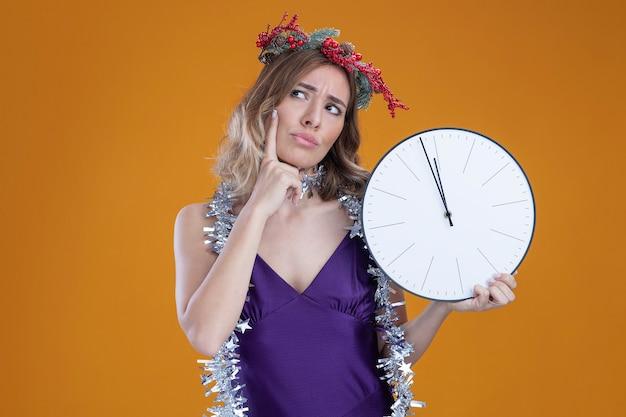 Pensando giovane bella ragazza che indossa abito viola e corona con ghirlanda sul collo tenendo l'orologio da parete mettendo il dito sulla guancia isolato su sfondo marrone