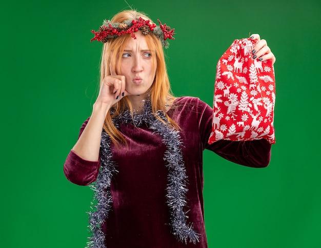 首に花輪と花輪と赤いドレスを着て、緑の背景で隔離の頬に手を置いてクリスマスバッグを見て考えている若い美しい少女
