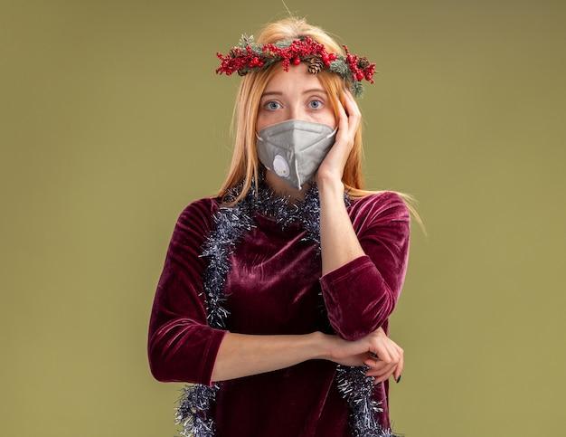 オリーブグリーンの背景で隔離の頬に手を置く花輪と花輪と医療マスクと赤いドレスを着ている若い美しい少女を考える
