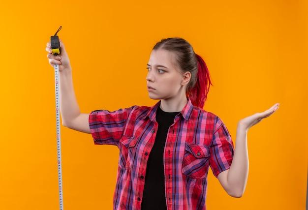Pensando giovane bella ragazza che indossa la camicia rossa guardando il metro a nastro in mano e sulla parete gialla isolata