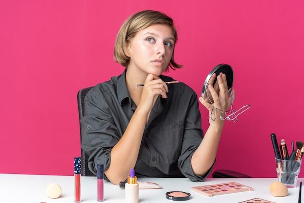 La giovane bella donna pensante si siede al tavolo con gli strumenti per il trucco che tengono il pennello per il trucco con lo specchio