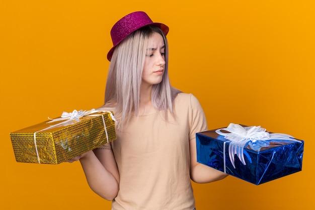 Думающая молодая красивая женщина в партийной шляпе держит и смотрит на подарочные коробки, изолированные на оранжевой стене