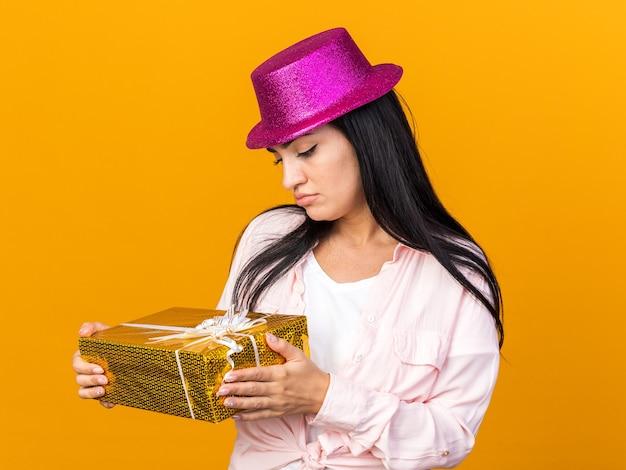 Pensando giovane bella donna che indossa un cappello da festa che tiene e guarda la confezione regalo isolata sulla parete arancione
